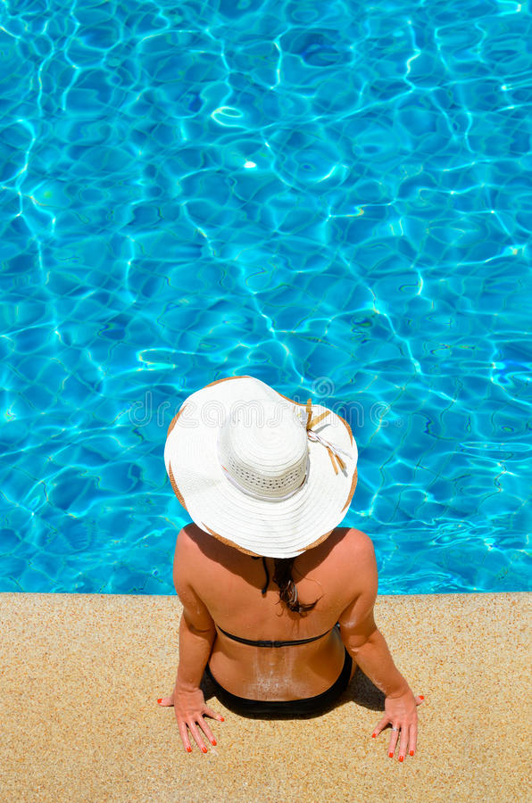 Mujer joven que se relaja por la piscina fotografía de archivo