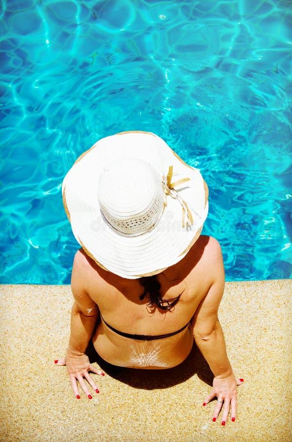 Mujer joven que se relaja por la piscina foto de archivo
