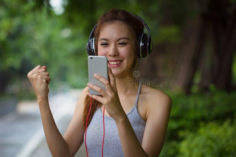 Mujer joven que se relaja y que canta mientras que música que escucha con el earp imágenes de archivo libres de regalías