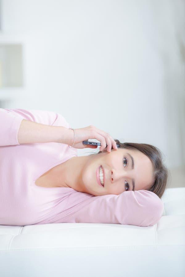 Mujer joven que se relaja y que llama por teléfono imagen de archivo libre de regalías