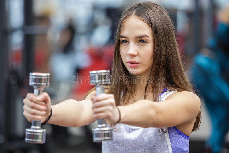 Mujer joven que se resuelve con dos pesas de gimnasia fotos de archivo libres de regalías