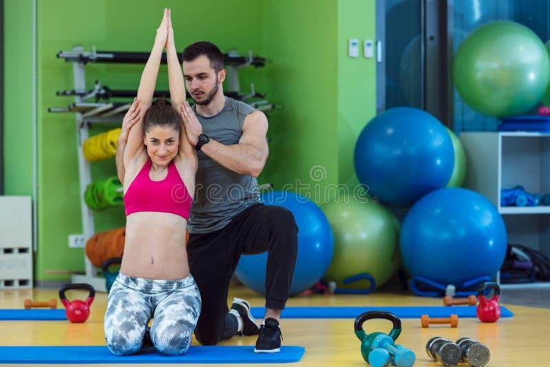 Mujer joven que se resuelve con el instructor personal en el gimnasio fotografía de archivo libre de regalías
