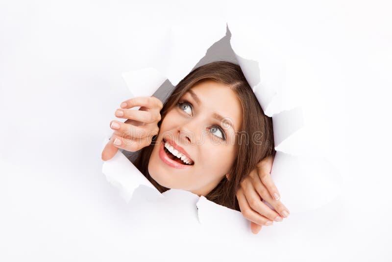 Mujer joven que se rompe a través de una hoja de papel fotos de archivo libres de regalías