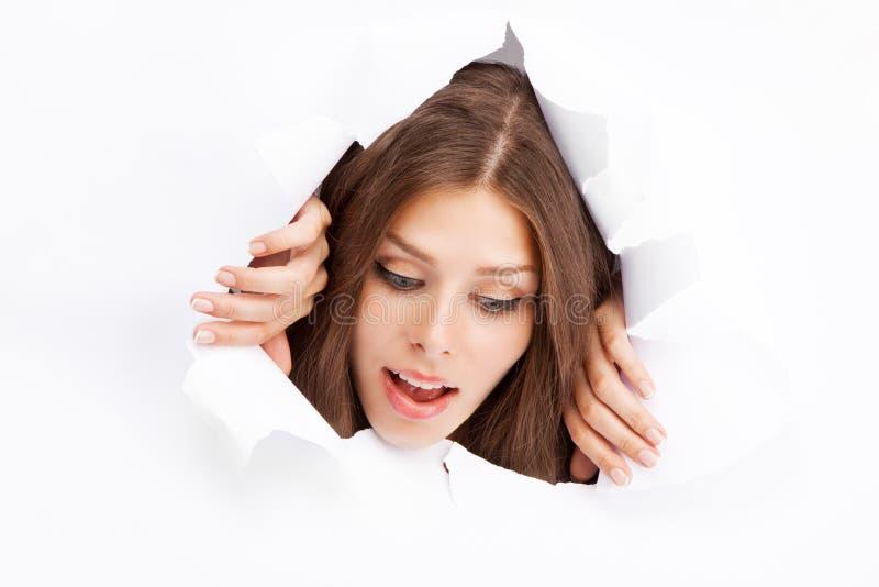 Mujer joven que se rompe a través de una hoja de papel fotos de archivo
