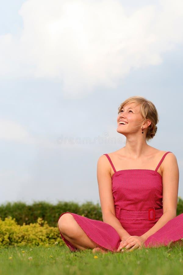 Mujer joven que se sienta al aire libre foto de archivo libre de regalías