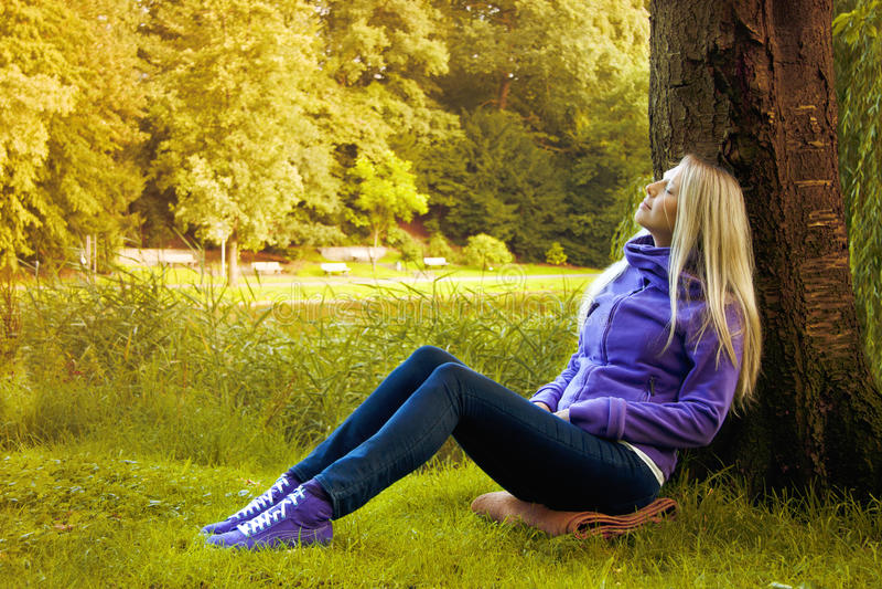 Mujer joven que se sienta bajo un árbol imagenes de archivo