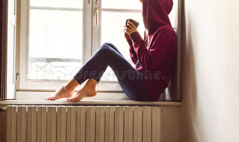 Mujer joven que se sienta cerca de la ventana que mira el café de consumición exterior en un humor nostálgico fotografía de archivo libre de regalías