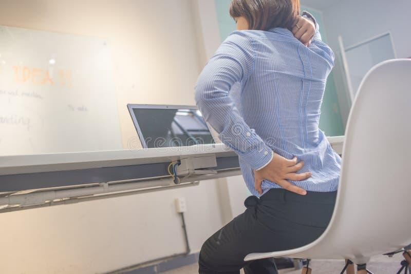 Mujer joven que se sienta con dolor de espalda en oficina imagenes de archivo