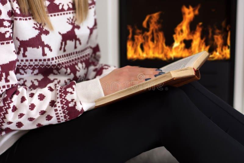 Mujer joven que se sienta delante de la chimenea y que sostiene el libro en las piernas y que lee en casa foto de archivo