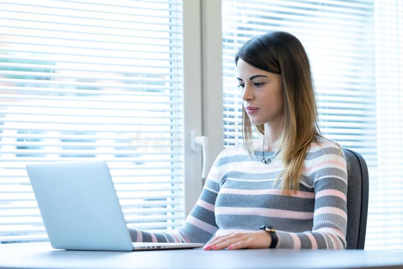 Mujer joven que se sienta delante de la computadora portátil imagenes de archivo