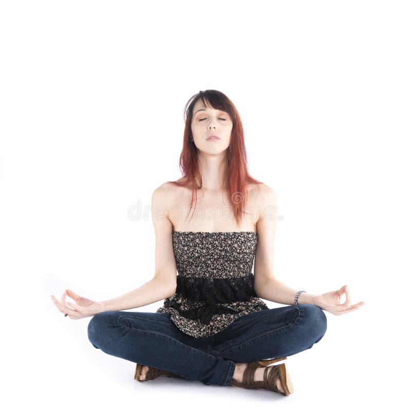 Mujer joven que se sienta en actitud de la yoga con los ojos cerrados foto de archivo