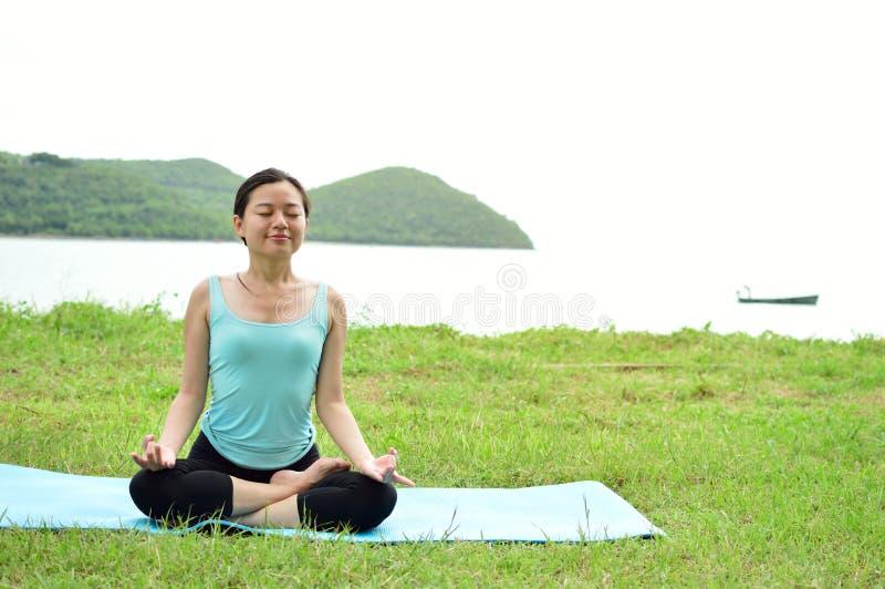 Mujer joven que se sienta en actitud de la yoga en cerca de la playa fotografía de archivo libre de regalías