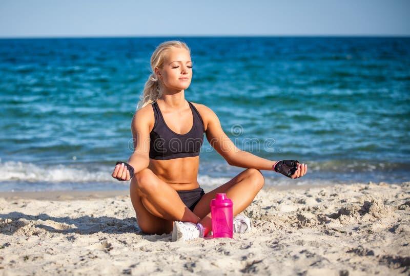 Mujer joven que se sienta en actitud de la yoga en la playa imágenes de archivo libres de regalías