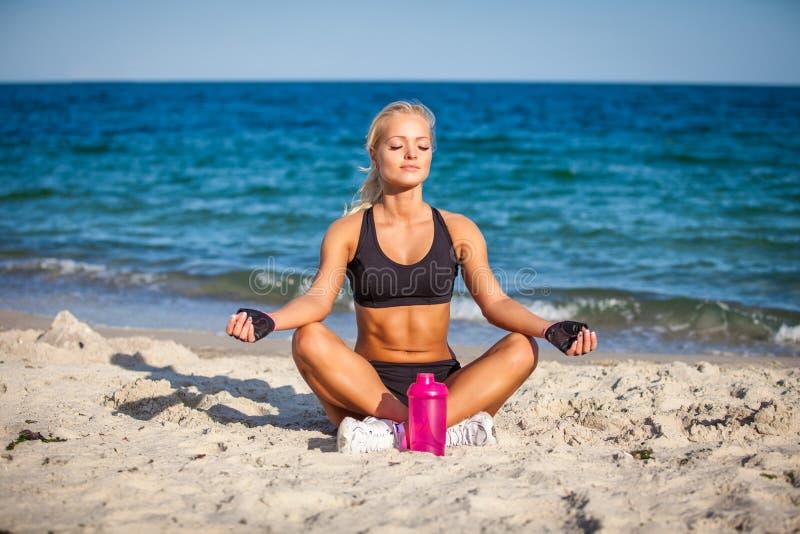 Mujer joven que se sienta en actitud de la yoga en la playa foto de archivo