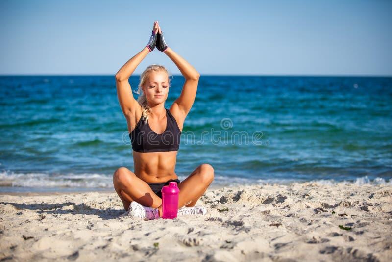 Mujer joven que se sienta en actitud de la yoga en la playa imagen de archivo libre de regalías