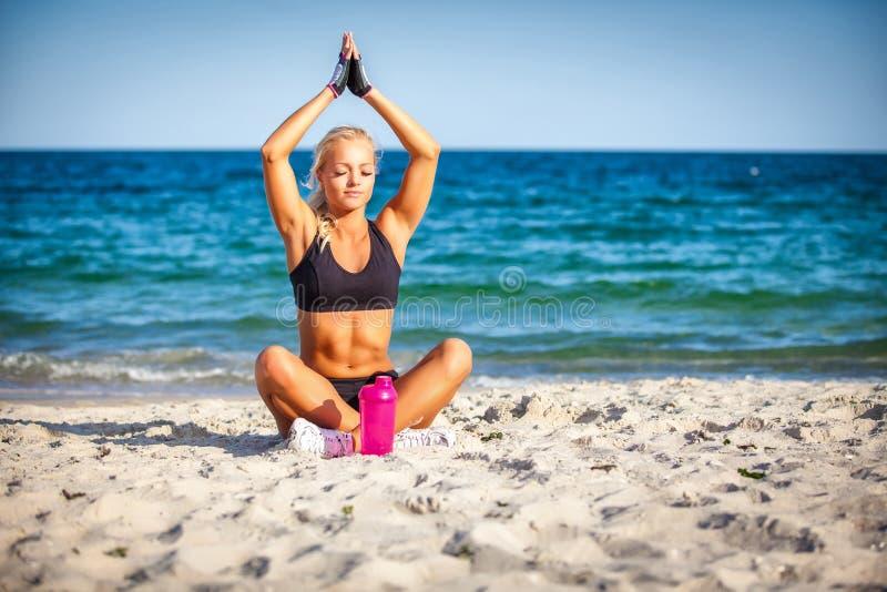 Mujer joven que se sienta en actitud de la yoga en la playa imagen de archivo