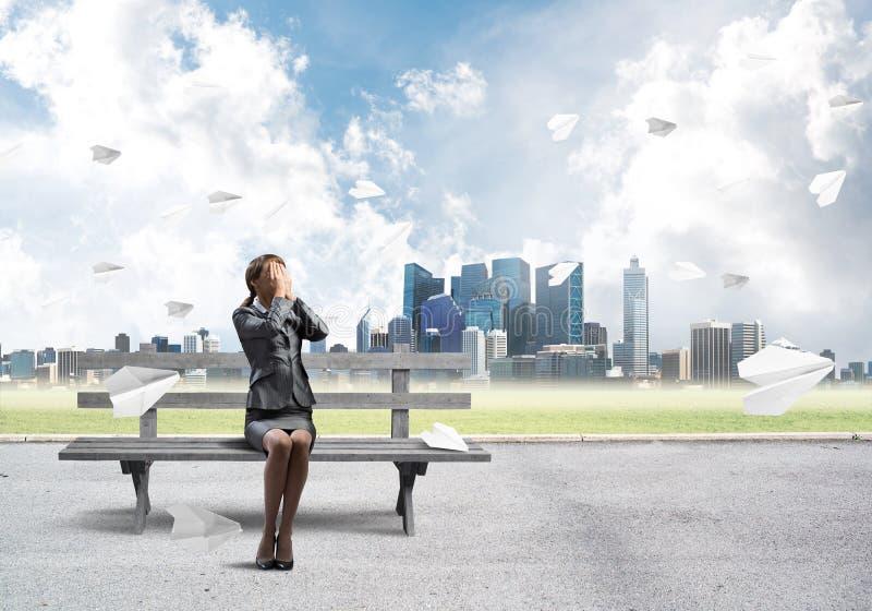 Mujer joven que se sienta en banco de madera al aire libre imagenes de archivo