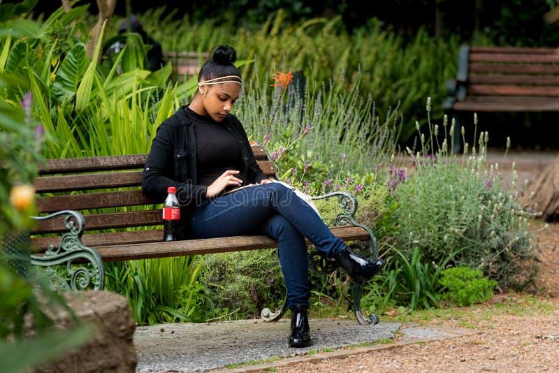 Mujer joven que se sienta en banco de parque usando una tableta o un teléfono foto de archivo