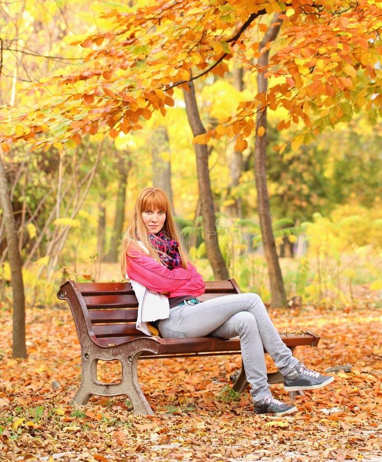 Mujer joven que se sienta en banco en parque foto de archivo libre de regalías