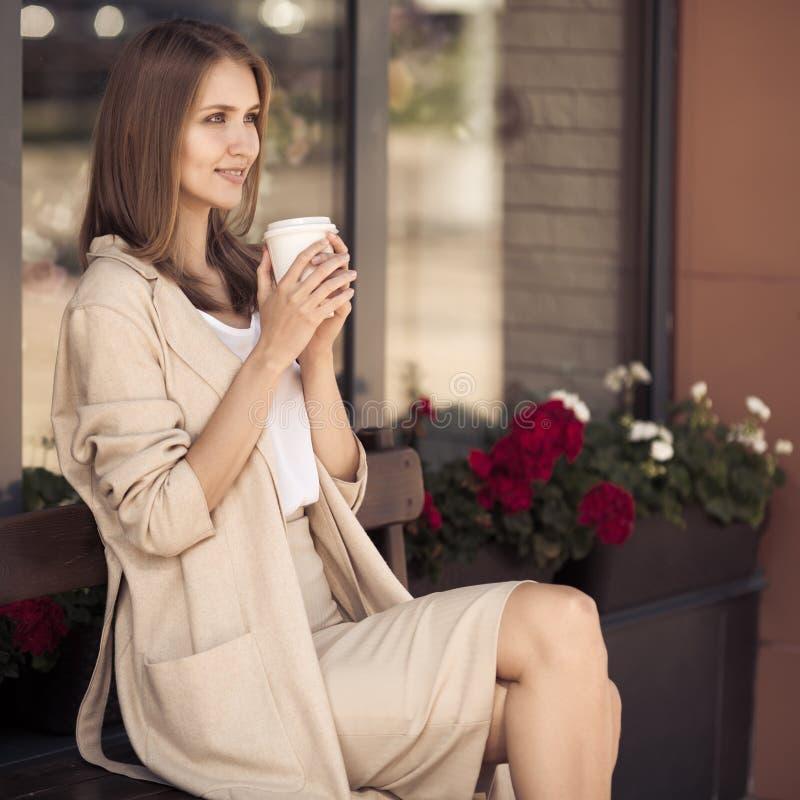 Mujer joven que se sienta en banco y el café de consumición imagen de archivo libre de regalías