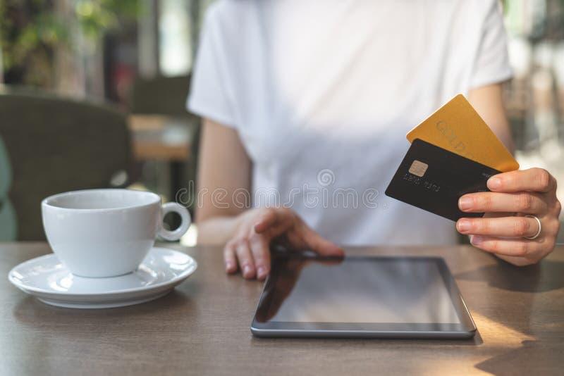 Mujer joven que se sienta en café y que usa la tarjeta moderna de la tableta y de crédito fotos de archivo libres de regalías