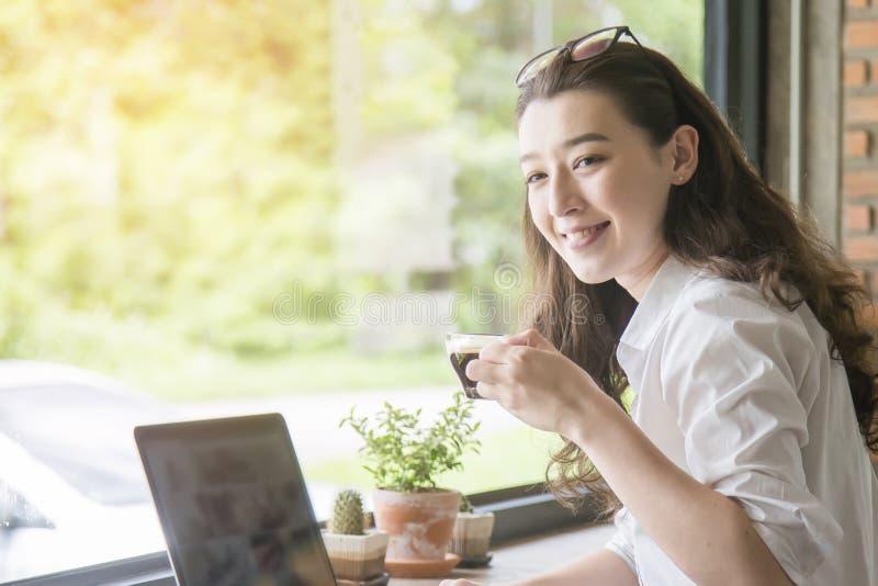 Mujer joven que se sienta en cafeter?a en la tabla de madera, el caf? de consumici?n y usando smartphone En la tabla es el ordena imagenes de archivo
