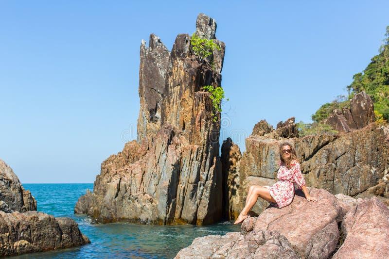 Mujer joven que se sienta en costa de mar de las rocas foto de archivo