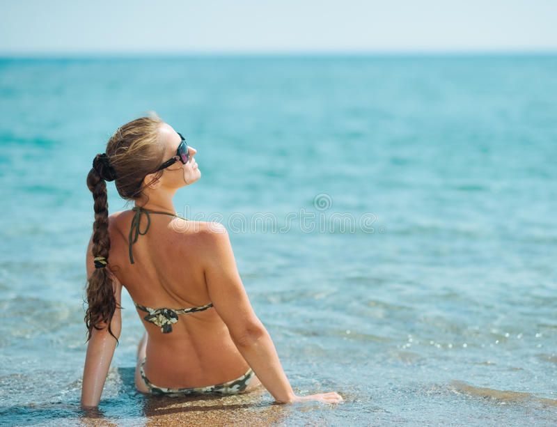 Mujer joven que se sienta en costa de mar. vista posterior foto de archivo