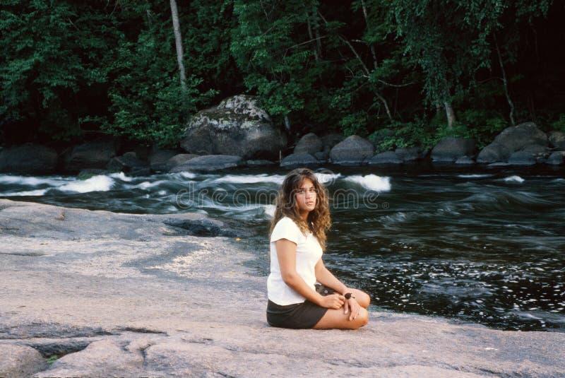 Mujer joven que se sienta en el banco de la corriente imagen de archivo libre de regalías