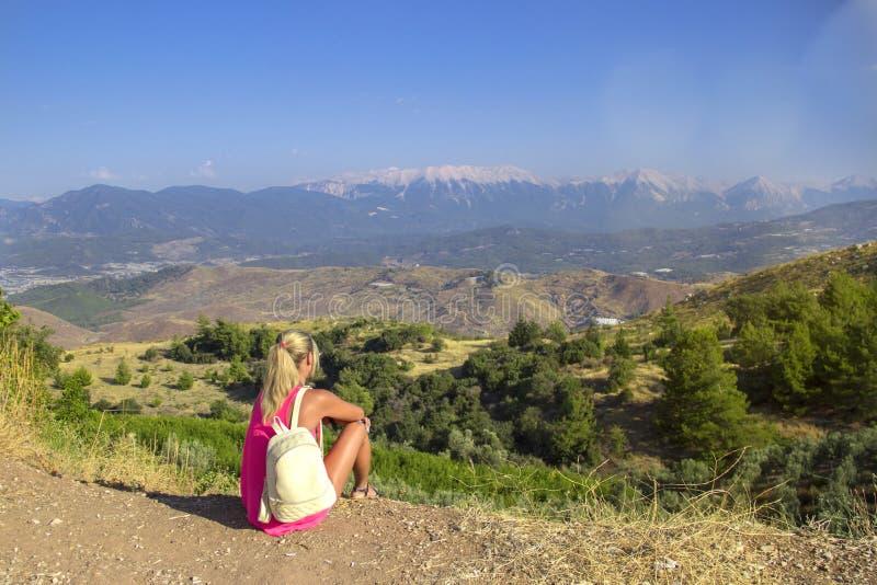 Mujer joven que se sienta en el borde del acantilado que mira sobre la vista expansiva de llanos y de montañas imagen de archivo