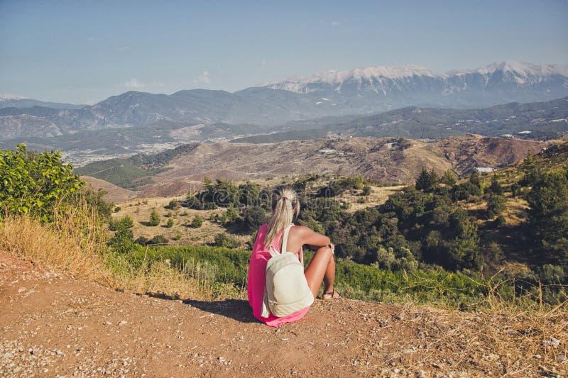Mujer joven que se sienta en el borde del acantilado que mira sobre la vista expansiva de llanos y de montañas fotos de archivo libres de regalías