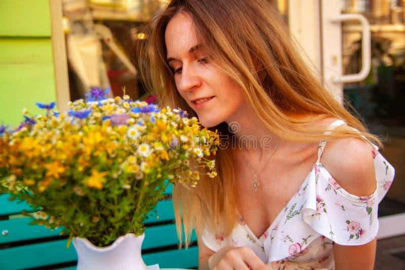 Mujer joven que se sienta en el café de la calle cerca de las flores y de las plantas verdes Concepto de lugar acogedor en aire a imágenes de archivo libres de regalías