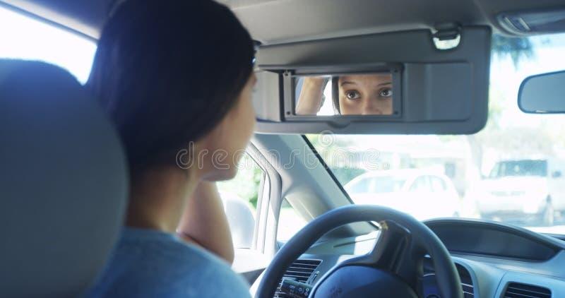 Mujer joven que se sienta en el coche que comprueba su maquillaje en espejo imagen de archivo