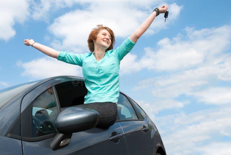 Mujer joven que se sienta en el coche y que lleva a cabo una llave contra SK azul fotografía de archivo libre de regalías