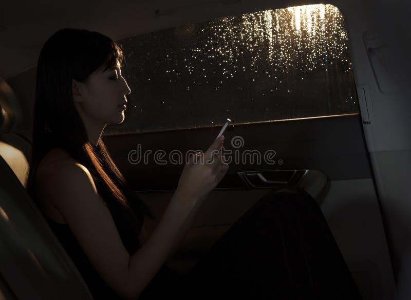 Mujer joven que se sienta en el coche y que manda un SMS en su teléfono en una noche lluviosa en Pekín foto de archivo libre de regalías