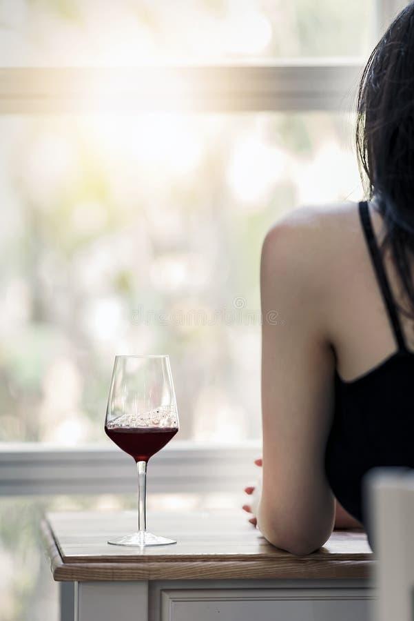 Mujer joven que se sienta en el escritorio con el vidrio de vino imagen de archivo libre de regalías