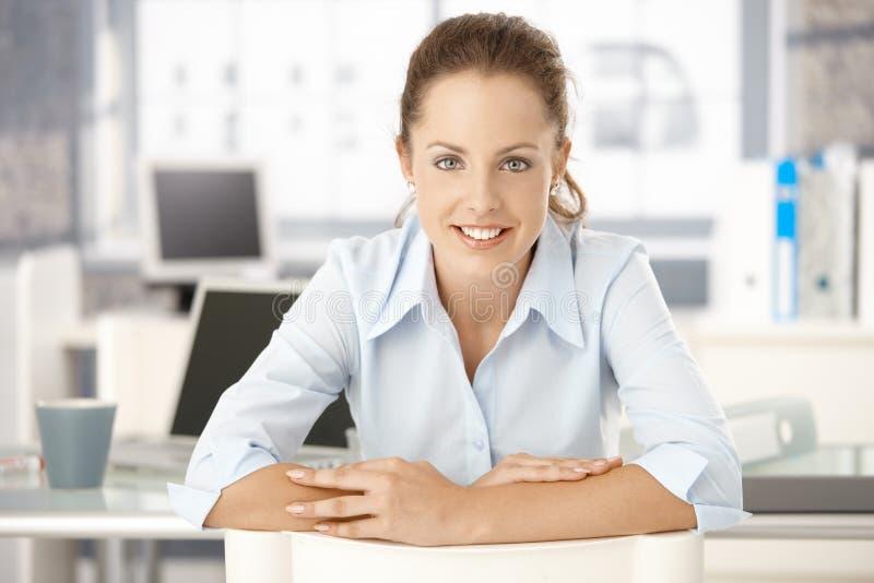 Mujer joven que se sienta en el escritorio en la sonrisa de la oficina imagenes de archivo