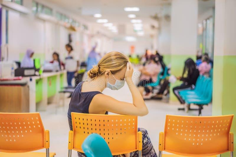 Mujer joven que se sienta en el hospital que espera la cita de un doctor Pacientes en sala de los doctores espera imagen de archivo