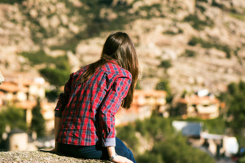 Mujer joven que se sienta en el hoyo de las montañas, mirando fijamente en el SP foto de archivo