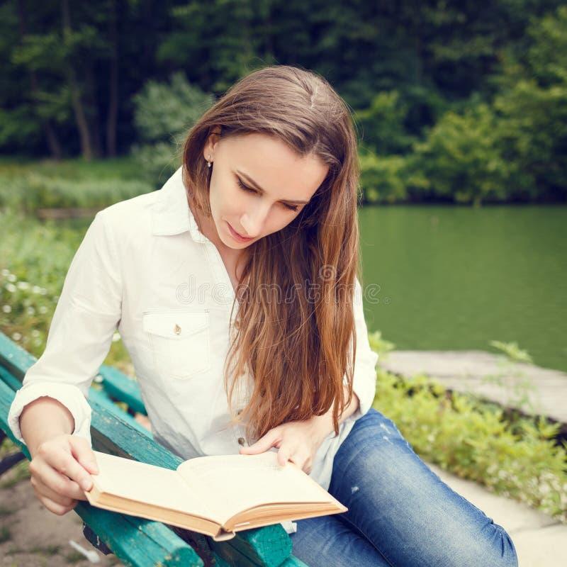 Mujer joven que se sienta en el libro del banco y de lectura imagen de archivo