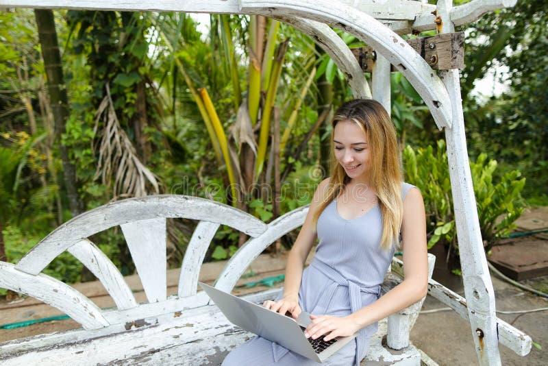Mujer joven que se sienta en el oscilación y que usa el ordenador portátil, palmas en fondo fotografía de archivo