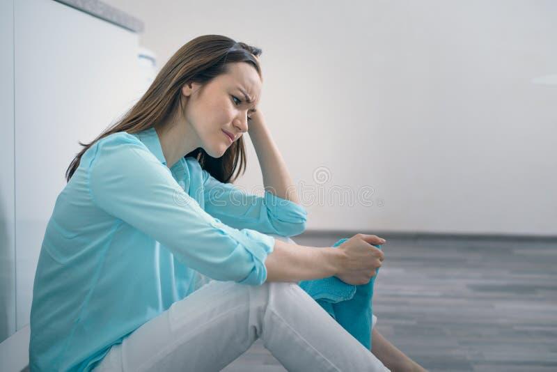 Mujer joven que se sienta en el piso de la cocina que lleva a cabo su cabeza y que llora, trastorno, triste, deprimido fotografía de archivo