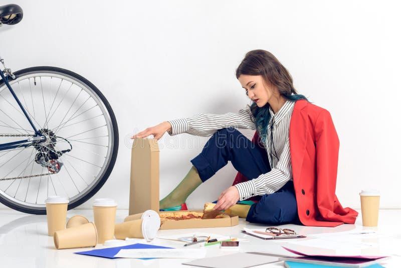 Mujer joven que se sienta en el piso y la caja de apertura con la pizza durante foto de archivo