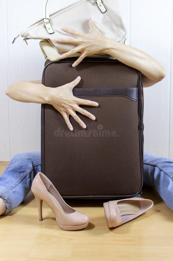 Mujer joven que se sienta en el piso y las abrazos, bolsos del equipaje de los abrazos foto de archivo libre de regalías