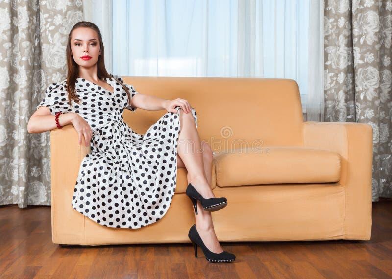 Mujer joven que se sienta en el sofá imagenes de archivo