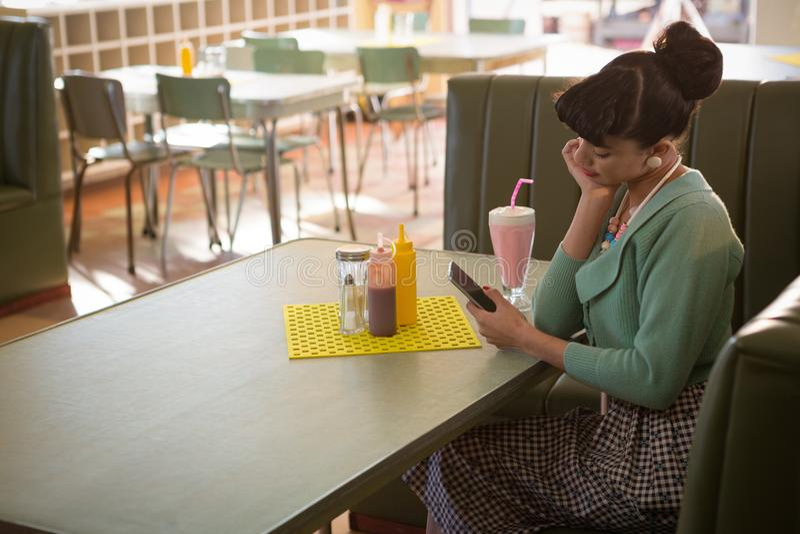 Mujer joven que se sienta en el sofá usando su teléfono móvil fotografía de archivo