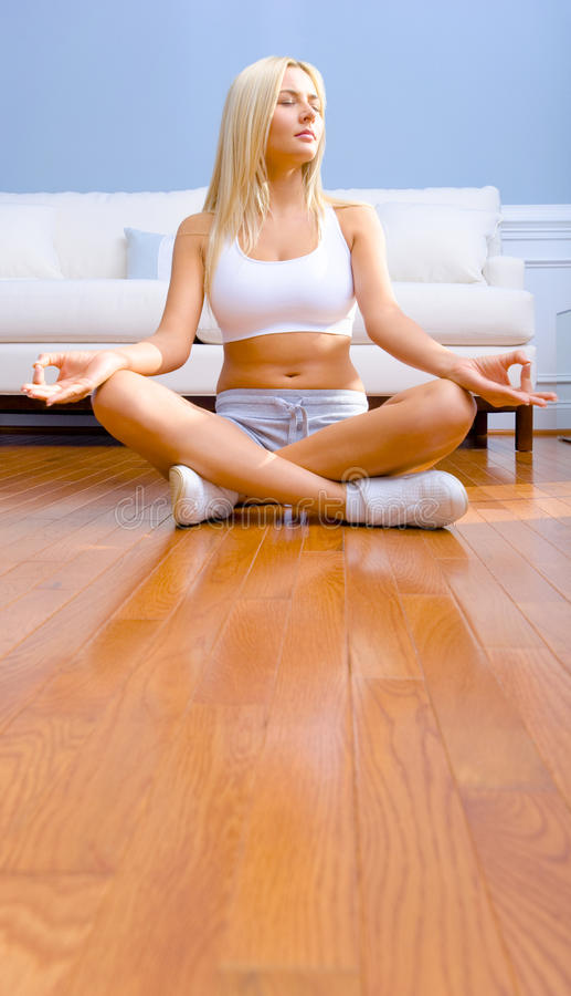 Mujer joven que se sienta en el suelo de madera Meditating fotos de archivo libres de regalías