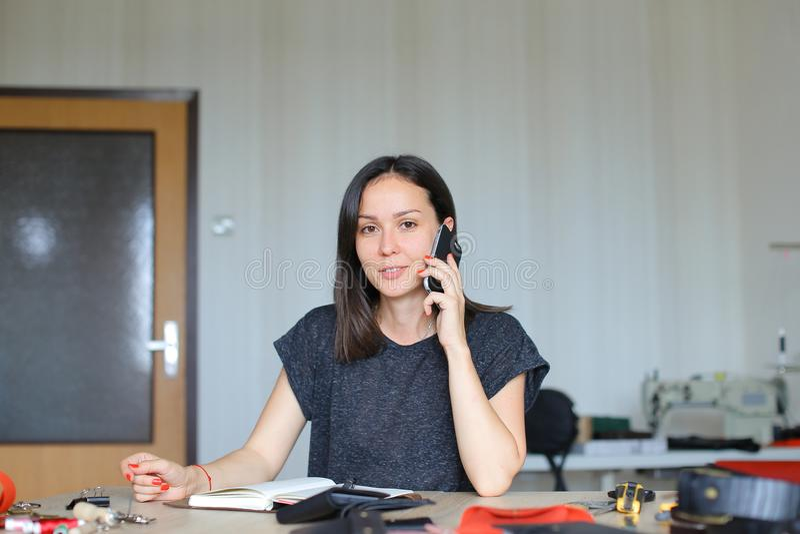 Mujer joven que se sienta en el taller de cuero y que hace el cuaderno hecho a mano y las carteras, hablando por smartphone fotografía de archivo