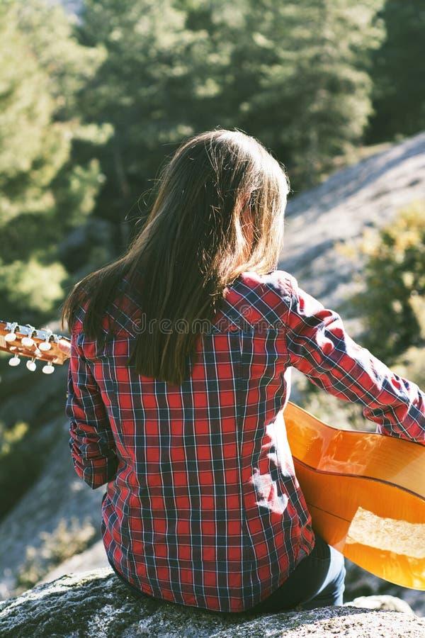 Mujer joven que se sienta en el top de la montaña, tocando la guitarra o fotos de archivo libres de regalías
