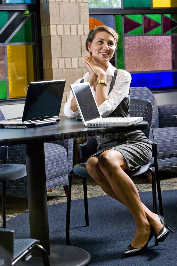Mujer joven que se sienta en el vector con el ordenador portátil fotografía de archivo libre de regalías